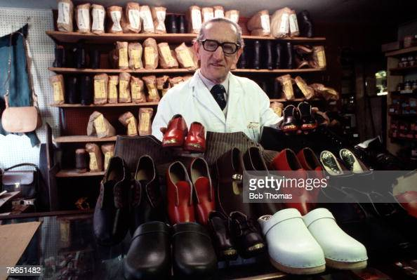 England Circa 1960's A Clogmaker is pictured with a collection of his work in his shop in Stockport
