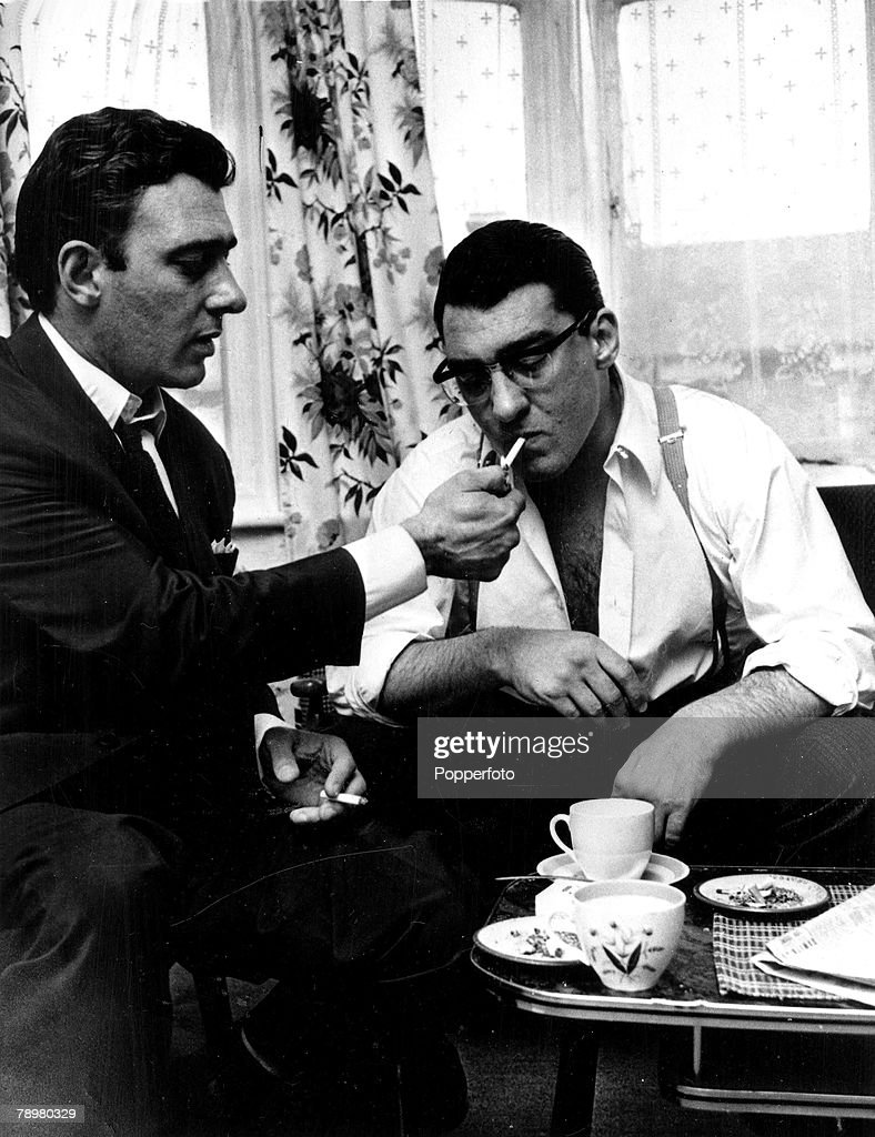 England, Circa 1969, East End London gangster Reggie Kray lights up a cigarette for his twin brother Ronnie as the two relax over a cup of tea in the front living room of their mother Violet+s house in Vallance Road, shortly before the trial in which they were charged with murder and sentenced to life in prison