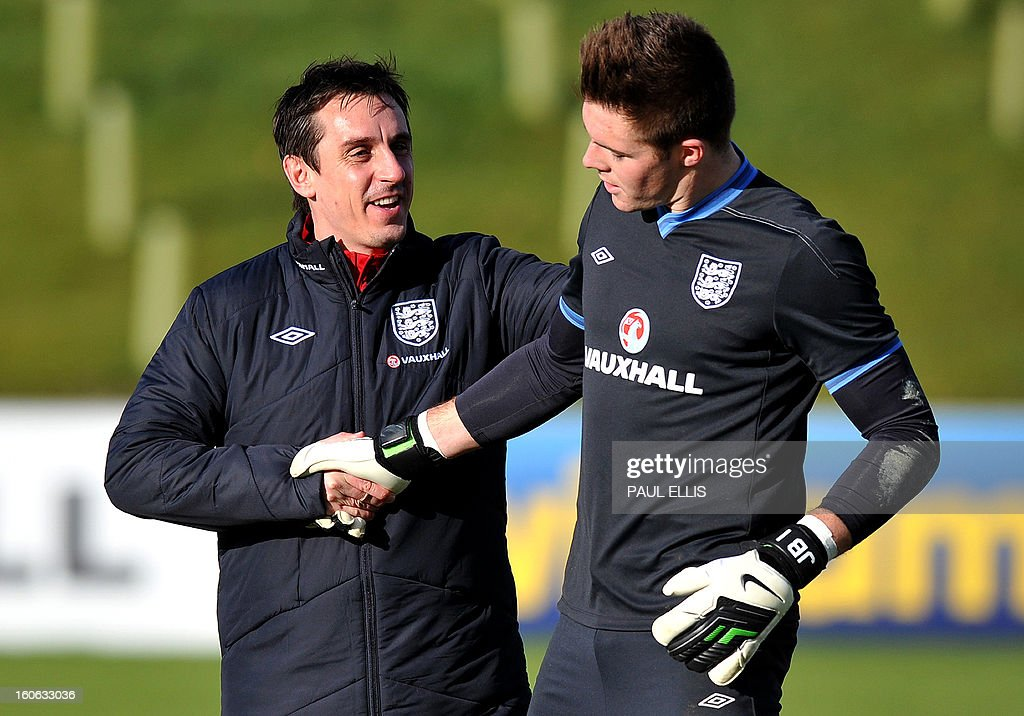England coach Gary Neville (L) shakes hands with England squad goalkeeper Jack Butland during a team training session at St George's Park in central England, on February 4, 2013. England take on Brazil at London's Wembley stadium in an international friendly on February 6. AFP PHOTO/Paul Ellis USE