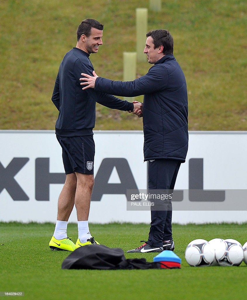 England coach Gary Neville (R) shakes hands with Steven Taylor during a training session at the St George's Park training complex, near Burton-upon-Trent, central England on March 19, 2013 ahead of their 2014 World Cup qualifier football match against San Marino on March 22.