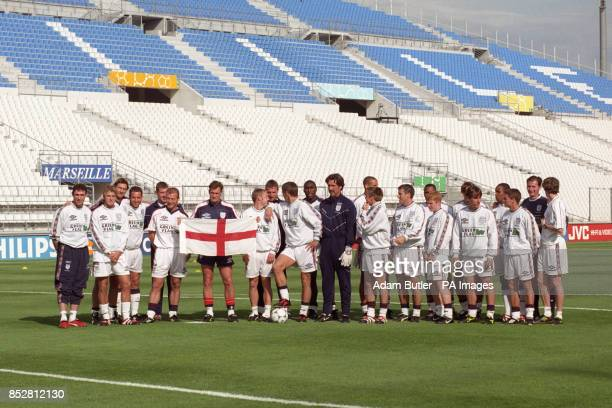 England coach Glenn Hoddle holds aloft the England flag as he poses with his team before the World Cup match against Tunisia at the Velodrome Stadium...