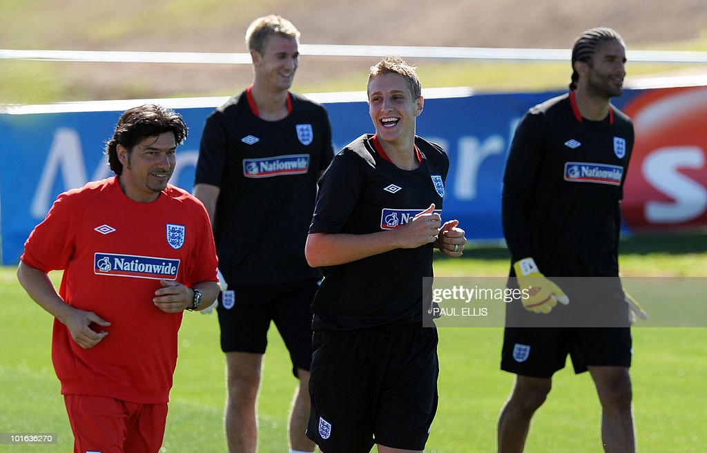 England coach Stefano Tirelli (L) runs with replacement defender Michael Dawson as he arrives for a training session at the Royal Bafokeng Sports Campus near Rustenburg on June 5, 2010. Dawson was flown from England to replace captain Rio Ferdinand after he injured his knee during the team's first training session in the country on June 4.