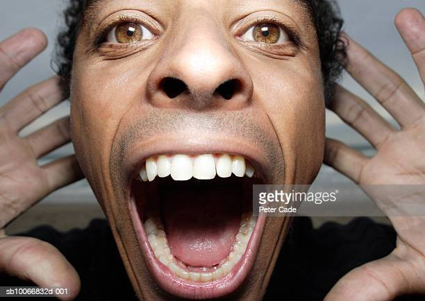 England, Cornwall, man with head between hands yelling, close up, portrait