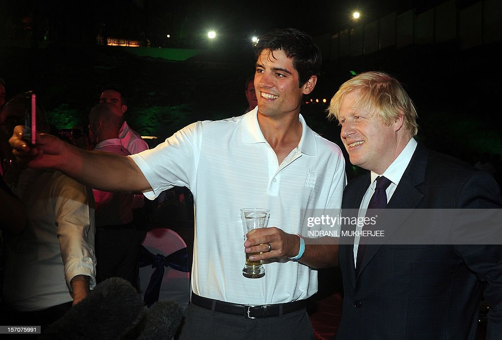 England cricket captain Alastair Cook takes a photograph of Mayor of London, Boris Johnson (R) and himself on his mobile phone at a reception in Mumbai on November 28, 2012. The British High Commissioner hosted a reception for the touring England cricket team attended by the Mayor of London, Boris Johnson who is currently in Mumbai as part of his 5 day-long three city India tour. AFP PHOTO/INDRANIL MUKHERJEE