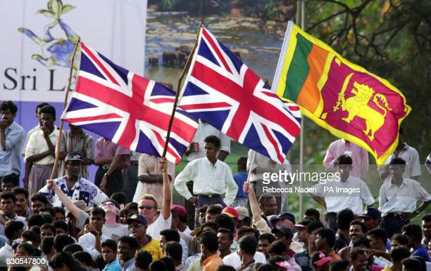 England cricket fans wave Union Jacks and the flag of Sri Lanka with local fans during the first Test match at the Galle International Cricket...