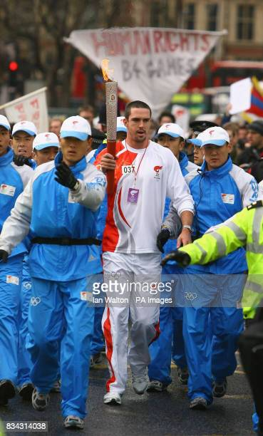 England cricket player Kevin Pietersen carries the Olmypic torch during its relay journey across London on its way to the lighting of the Olympic...