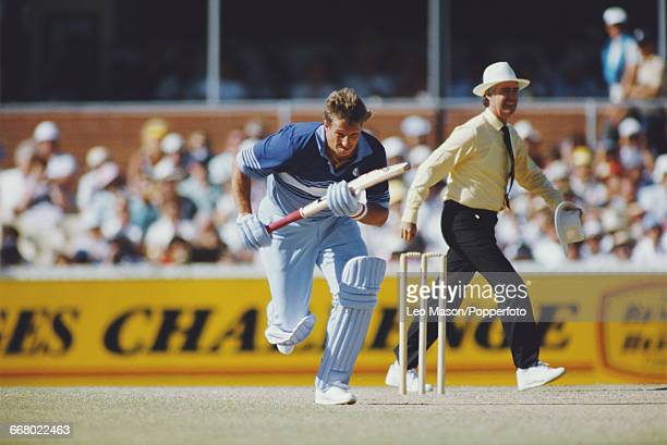 England cricketer Ian Botham runs from the crease during play against Australia in the Benson Hedges Challenge one day international cricket...