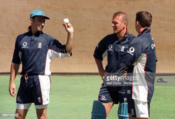 England cricketer Nasser Hussain holds up a white day/night cricket ball to teammates Alec Stewart and Darren Gough during net practice at the...