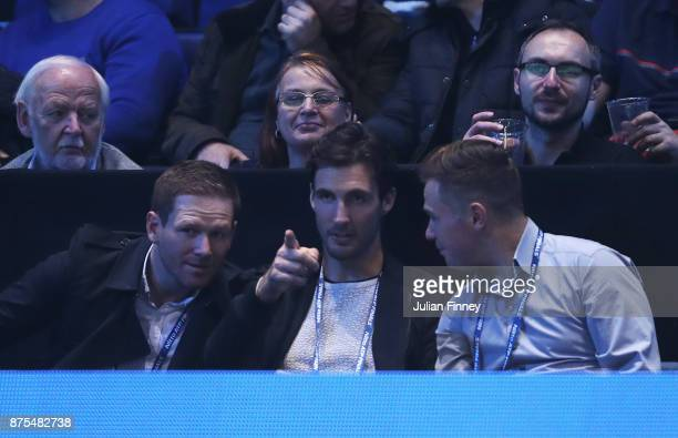 England cricketers Eoin Morgan and Steven Finn watch the match between Grigor Dimitrov of Bulgaria and Pablo Carreno Busta of Spain during day six of...