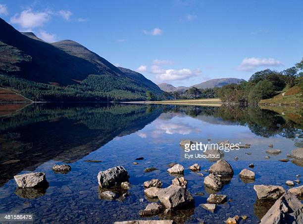 England Cumbria Lake District Buttermere Landscape blue sky and drifting cloud reflected in lake with small rocks protruding from clear shallow water...