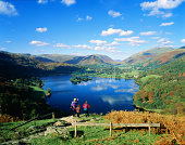 England, Cumbria, Lake District, hikers looking over Lake Grasmere