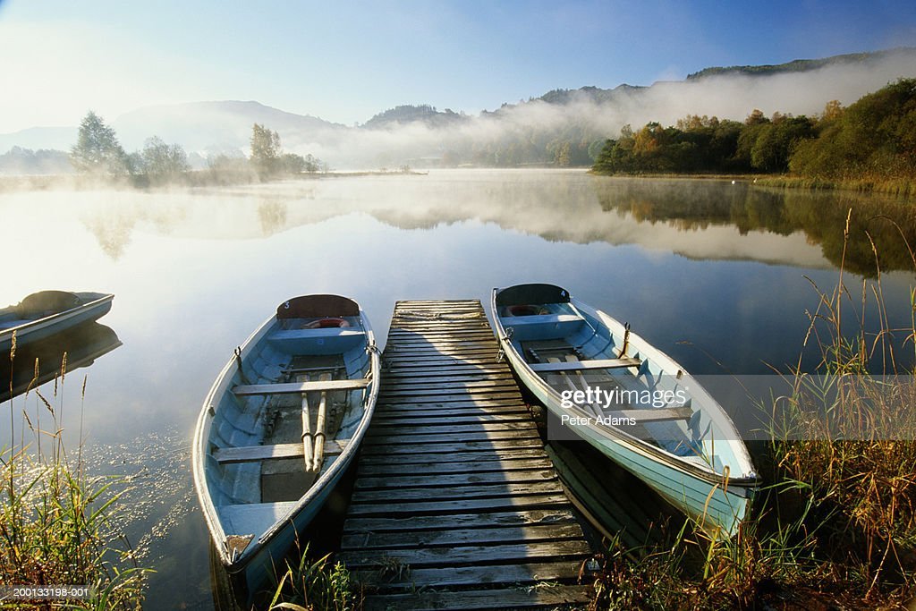 England, Cumbria, two boats either side of boardwalk on Lake Grasmere : Stock Photo