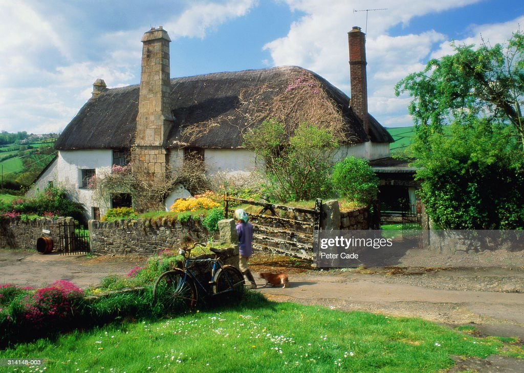 England, Devon, Dartmoor, Chagford, woman and dog at thatched cottage : Stock Photo