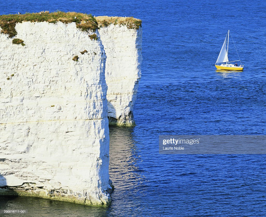 UK, England, Dorset, small sailing boat near white cliffs