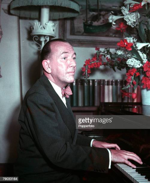 England English dramatist actor and composer Noel Coward is pictured playing the piano