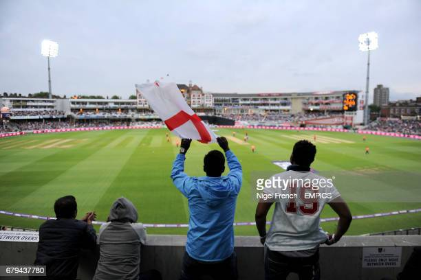 A England fan waves a flag as he and others watch the action from the stands