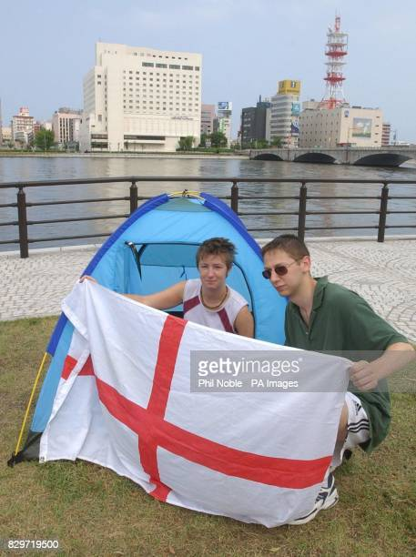 England fans Eddie Richards from London and Judith Earle from Newcastle Upon Tyne sit on the banks of the Shinano River in Niigata where they slept...