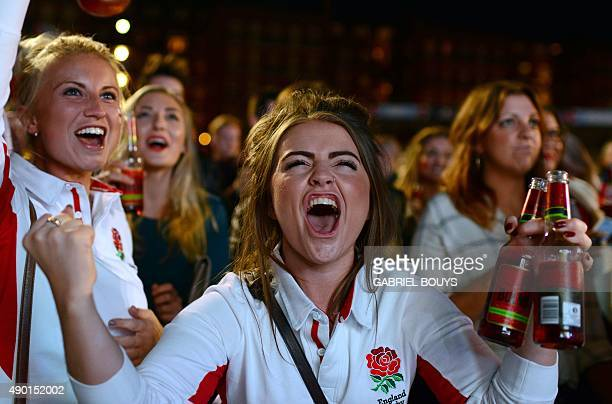 England fans react as they watch the England v Wales rugby union game on a giant television screen at a fanzone in Cardiff Wales on September 26...