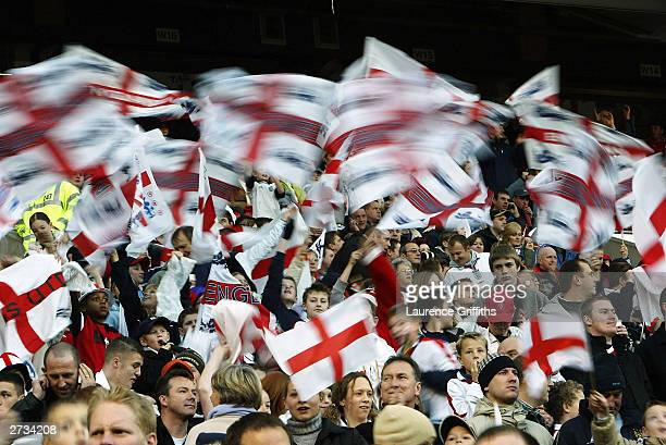 England fans wave flags during the International Friendly match between England and Denmark at Old Trafford on November 16 2003 in Manchester England