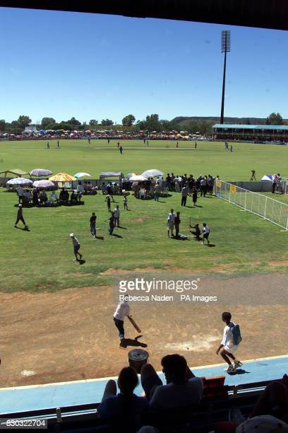 England field against Zimbabwe in front of the slag heaps of the Diamond Mines at Kimberley and children playing their own game of cricket during the...