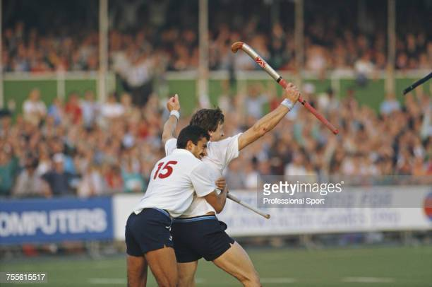 England field hockey player Imran Sherwani hugs teammate Sean Kerly after Kerly scored a goal for England during competition in the 1986 Men's Hockey...