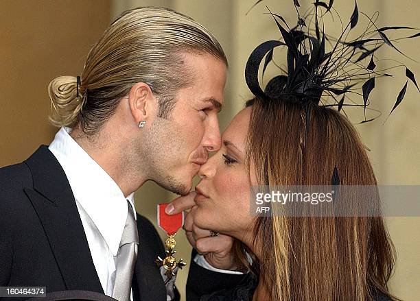 England football captain David Beckham kisses his wife Victoria as he holds the OBE he received 27 November 2003 from Britain's Queen Elizabeth II at...