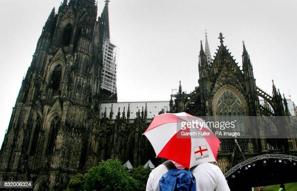 England football fans take shelter from rain next to the cathedral in Cologne Germany before England's third match of their World Cup campaign againt...