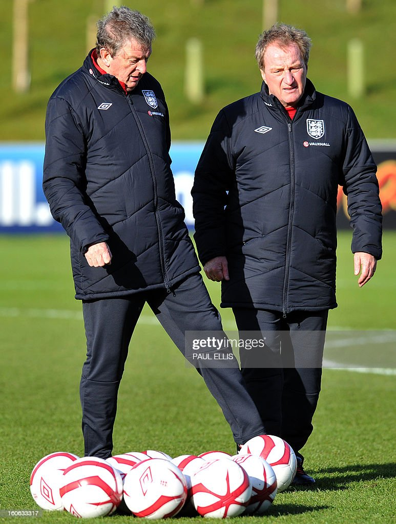 England football manager Roy Hodgson (L) and coach Ray Lewington speak during a training session at the St George's Park training complex near Burton-upon-Trent, central England on February 4, 2013. England take on Brazil at Wembley in an international friendly on February 6. AFP PHOTO/Paul Ellis EDITORIAL