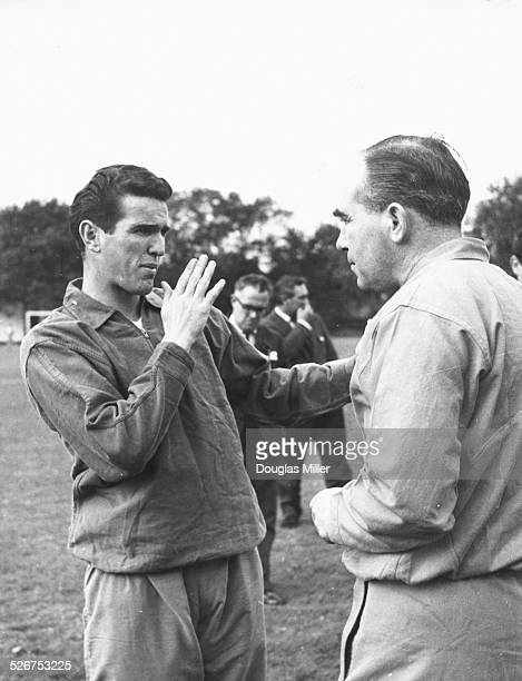 England football player Terry Paine animatedly talking to team manager Alf Ramsey during training prior to the England match against the 'rest of the...
