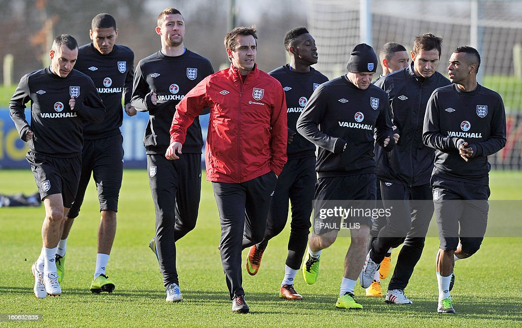 England football players train with coach Gary Neville (4th L) during a training session at St George's Park in central England, on February 4, 2013. England take on Brazil at London's Wembley stadium in an international friendly on February 6. AFP PHOTO/Paul Ellis/ NOT
