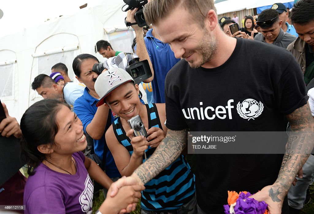 England football superstar <a gi-track='captionPersonalityLinkClicked' href=/galleries/search?phrase=David+Beckham&family=editorial&specificpeople=158480 ng-click='$event.stopPropagation()'>David Beckham</a> (R) greets survivors of devastating Typhoon Haiyan during a visit to a tent city in Tacloban city, Leyte province, central Philippines on February 13, 2014. Beckham visited the Philippines on February 13 to give comfort to survivors of the Asian country's deadliest ever typhoon -- although not everyone was sure of his identity. AFP PHOTO / TED ALJIBE