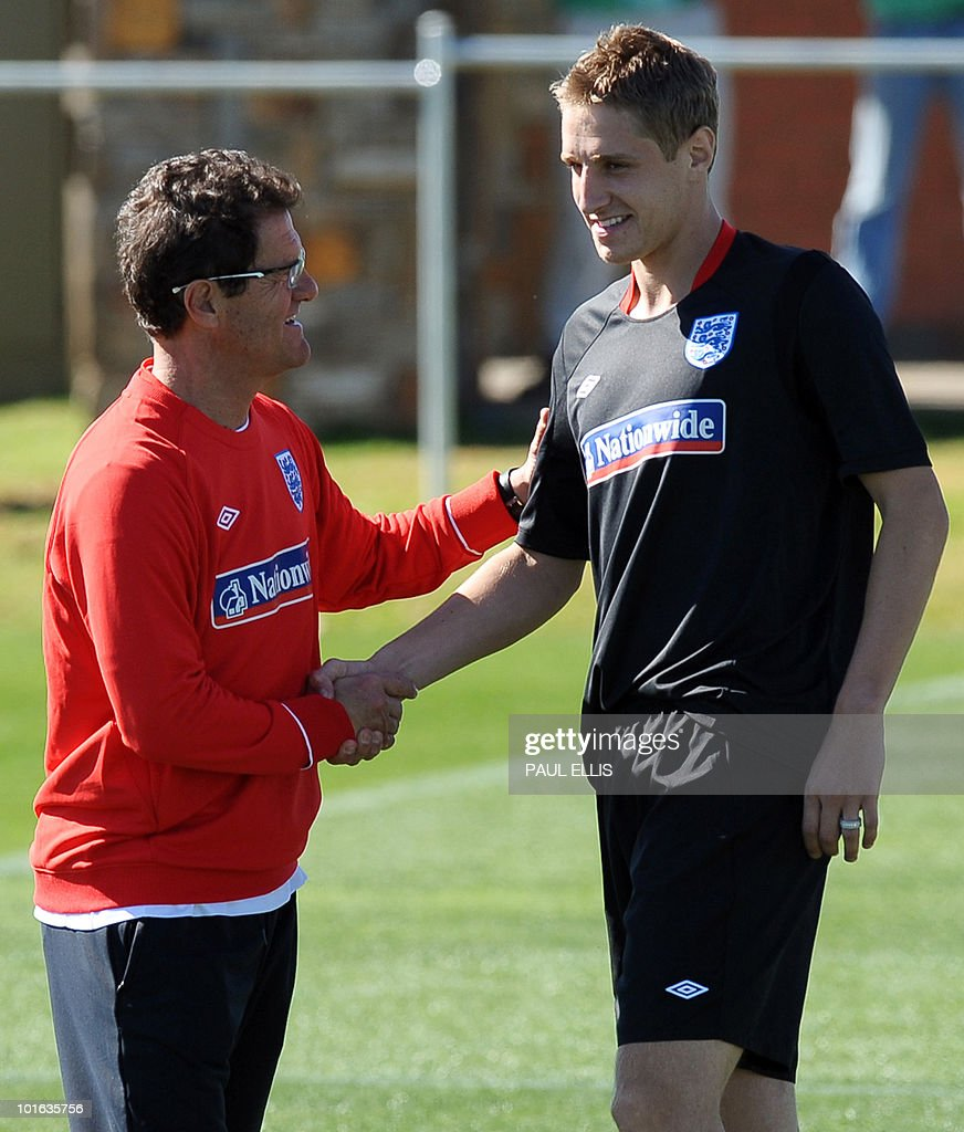 England football team manager Fabio Capello (L) welcomes replacement defender Michael Dawson as he arrives for a training session at the Royal Bafokeng Sports Campus near Rustenburg on June 5, 2010. Dawson was flown from England to replace captain Rio Ferdinand after he injured his knee during the team's first training session in the country prior to the World Cup 2010 kick-off in South Africa.