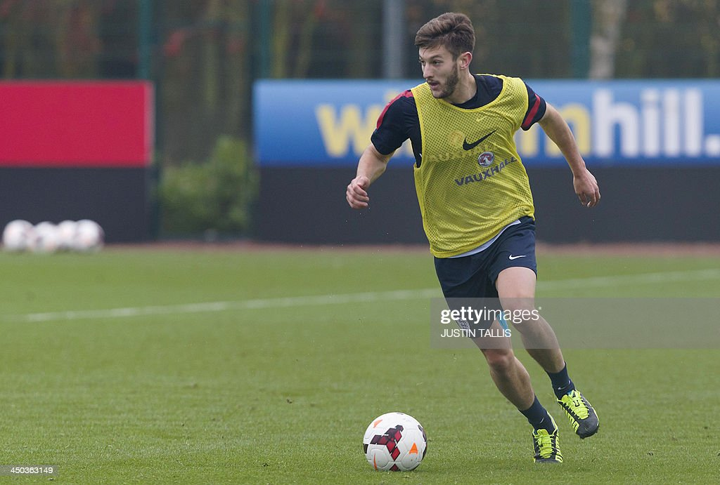 England football team player Adam Lallana dribbles the ball during an England training session at Arsenal's training ground, London Colney, north of London on November 18, 2013 ahead of their forthcoming international friendly football match against Germany.