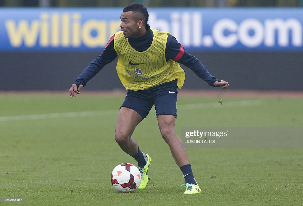 England football team player Ashley Cole dribbles the ball during an England training session at Arsenal's training ground, London Colney, north of London on November 18, 2013 ahead of their forthcoming international friendly football match against Germany.