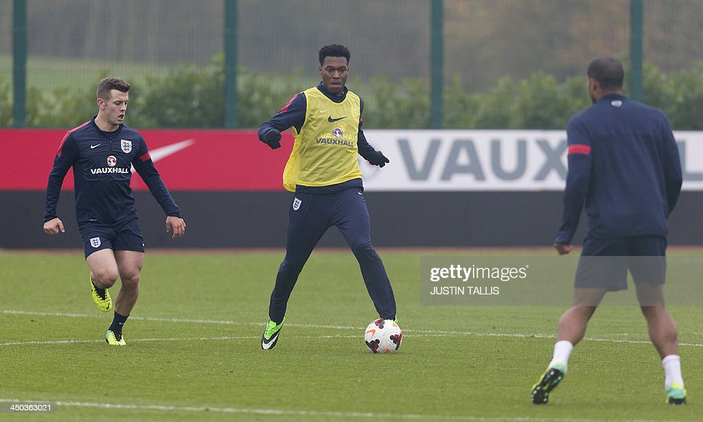 England football team player Daniel Sturridge (C) dribbles the ball during an England training session at Arsenal's training ground, London Colney, north of London on November 18, 2013 ahead of their forthcoming international friendly football match against Germany.
