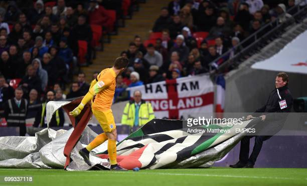 England goalkeeper Jack Butland helps a groundsman remove a banner which had blown onto the pitch due to high winds