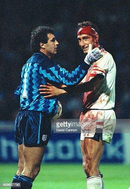 England goalkeeper Peter Shilton and bloodied defender Terry Butcher celebrate after a goaless draw between Sweden and England in a 1990 FIFA World...