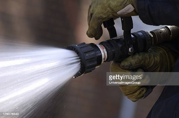 England Hertfordshire Firefighter holding hose closeup of hands A fire fighter from the Hertfordshire Fire Rescue Service UK grasping a hose nozzle...