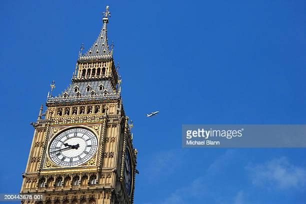 England, London, Big Ben, aeroplane flying in blue sky in background
