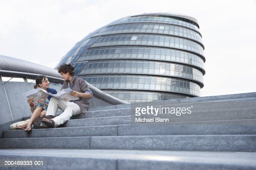 'England, London, City Hall, couple sitting on steps' : Stock Photo