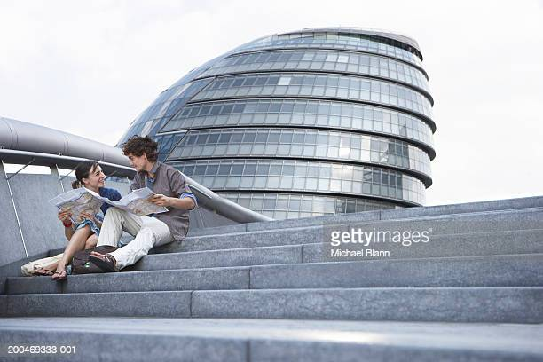 'England, London, City Hall, couple sitting on steps'