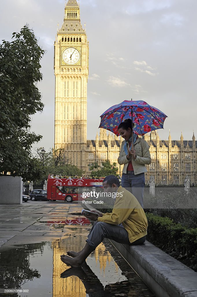 England, London, couple looking at map, woman with umbrella : Stock Photo