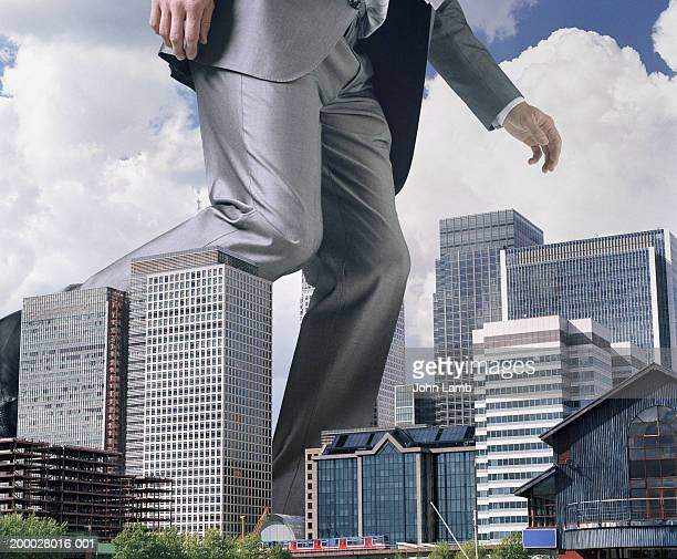England, London, Docklands, giant man passing offices, low section