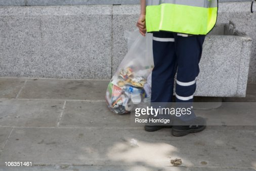 England, London, man holding bin bag filled with rubbish : Stock Photo