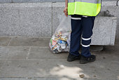 England, London, man holding bin bag filled with rubbish