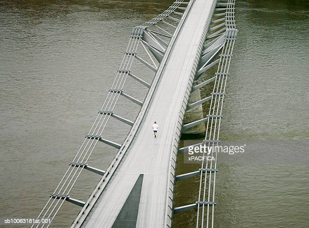 England, London, man jogging on Millennium Bridge, aerial view