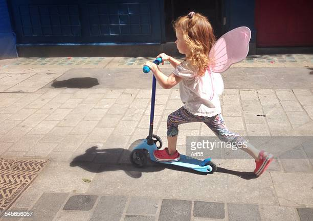 UK, England, London, Portrait of girl (2-3) with fairy wings riding scooter on city pavement
