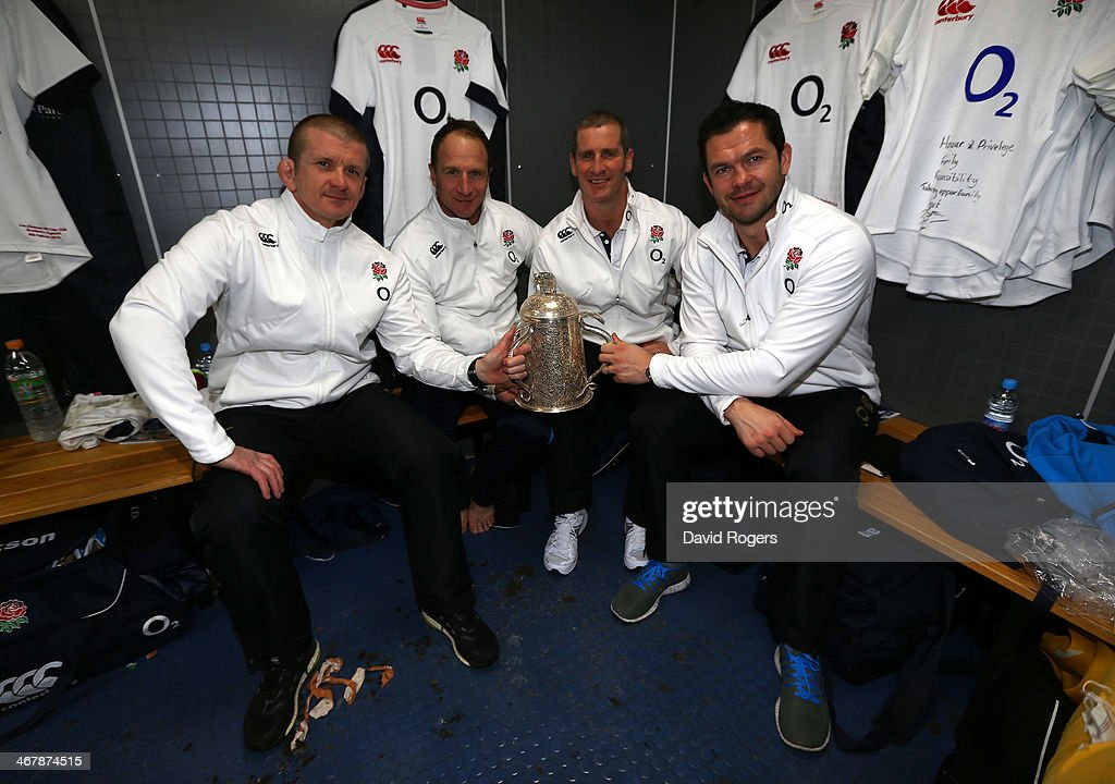 England management Graham Rowntree Mike Catt head coach Stuart Lancaster and Andy Farrell pose in the dressing room with The Calcutta Cup after...