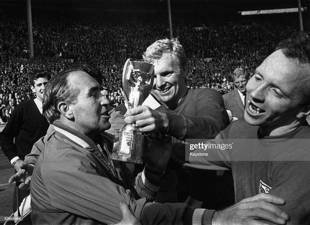 England Manager Alf Ramsey (left) celebrates his team's 4-2 victory in extra time over West Germany in the World Cup Final at Wembley Stadium. With him is captain Bobby Moore (1941 - 1993), holding the Jules Rimet Trophy, and team mate Nobby Stiles, 30th July 1966.