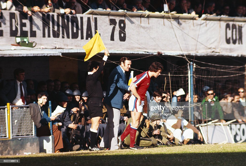 England manager Don Revie holds back player Trevor Cherry after the defnder had two front teetch knocked out before being sent off later in the match...